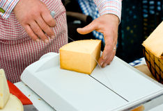 Cheese Slicing. Shop keeper slicing cheese with wire cutter board Royalty Free Stock Photos
