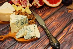 Cheese snack with fruits. Different gourmet refined varieties of cheese - like roquefort, camembert and parmesan - with grapefruit, garnet and walnuts - perfect Stock Photo