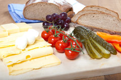 Cheese snack with german bread, mozzarella, cherry tomatoes, cucumber, grapes Royalty Free Stock Photos