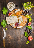 Cheese snack Gorgonzola and Camembert with  wine glass honey knife cheese grapes on a branch with leaves Peaches on wooden rustic Stock Photo