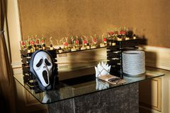 Cheese snack, plates, cutlery, mask arranged on table. Cheese snack, plates, cutlery, scary mask arranged on glass table on catering service banquet stock photo