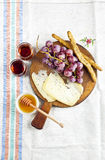 Cheese snack on a wooden board with grapes, bread sticks and Ita Royalty Free Stock Images