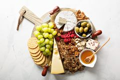 Cheese and snacks plate on white background. Overhead shot stock image