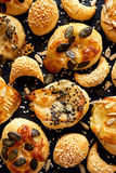 Cheese snacks with puff pastry sprinkled with a mix of seeds on a black background Royalty Free Stock Image