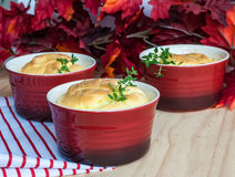 Cheese souffle in red ramekins stock image