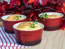 Cheese souffle in red ramekins Stock Image