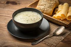 Cheese soup in a black plate on the rustic background. Stock Photos
