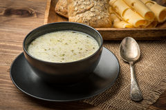 Cheese soup in a black plate on the rustic wooden background. Cheese soup in a black plate on the  wooden background Royalty Free Stock Photography