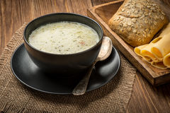 Cheese soup in a black plate on the rustic wooden background. Cheese soup in a black plate on the  wooden background Royalty Free Stock Image