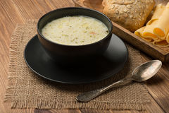 Cheese soup in a black plate on the rustic wooden background. Cheese soup in a black plate on the brown wooden background Royalty Free Stock Photos