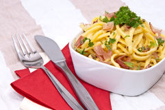 Cheese Spaetzle on red striped tablecloth Royalty Free Stock Images