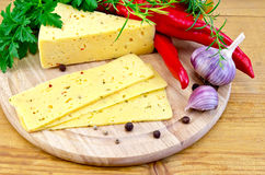Cheese with spices and herbs on a round board Royalty Free Stock Photography
