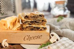 Cheese square cake. With mushrooms cheese and parsley and greens next to a large and juicy piece of yellow cheese cut into slices on a wooden stand stock photo