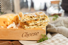 Cheese square cake. With cheese and parsley and greens next to a large and juicy piece of yellow cheese Puff pastry cake on a wooden stand central shoot Stock Photography