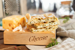Cheese square cake. Cheese square pie with cheese and parsley and greens next to a large and juicy piece of yellow cheese on a wooden stand stock images