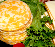 Cheese Stacks With Lettuce. Round and square stacks of cheese with green leafy lettuce Royalty Free Stock Photos
