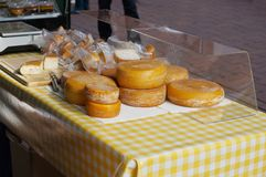 Cheese stall at an open-air farmers market. Cheesemonger stand with rounds of Gouda and other cheeses at an open-air farmers market royalty free stock photo