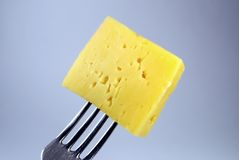 Cheese and steel fork Stock Photos