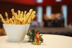 Cheese sticks with Christmas decoration. On cocktail table. Background is blurred Christmas event stage with presents on a table Royalty Free Stock Photography