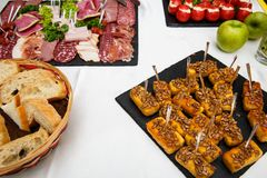 Cheese sticks. Food tray with delicious salami, pieces of sliced ham, sausage, salad. Bread. Tomatoes stuffed with cheese and garl. Ic - Meat platter with Stock Image