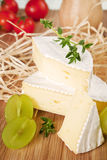 Cheese still life. Cut camembert piece, grapes and tomatos arranged on wooden board Royalty Free Stock Photography