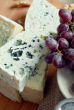 Cheese still life with red grapes and walnuts Royalty Free Stock Photography