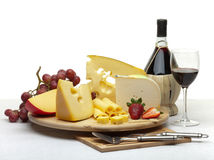 Cheese still life on a wooden round. Composition of cheese, grapes, bottles and glasses of wine and strawberries on a wooden round tray on a white tablecloth Royalty Free Stock Images