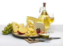 Cheese still life on a wooden round. Composition of cheese, grapes, bottles and glasses of wine and strawberries on a wooden round tray on a white tablecloth royalty free stock photo