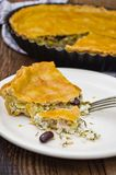 Cheese tart with leek and red beans. Salty tart with feta cheese, leek and red beans on a wooden board. Showing a separate slice on a plate royalty free stock photos