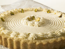 Cheese Tart with pistachio nuts and whipped cream. On a white background Royalty Free Stock Image