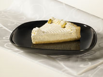 Cheese Tart with pistachio nuts and whipped cream. On a white background Stock Photos