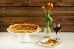 Cheese tart with red wine and red tulips on wooden background Royalty Free Stock Photo