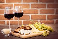 Cheese, toasted brown bread, two glasses of red wine. Horizontal Royalty Free Stock Photos