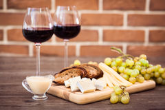 Cheese, toasted brown bread, two glasses of red wine. Horizontal Royalty Free Stock Photo
