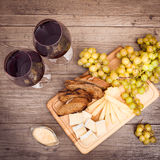 Cheese, toasted brown bread, two glasses of red wine. Horizontal. Cheese, toasted brown bread, two glasses of red wine. Top view. Horizontal Royalty Free Stock Photography