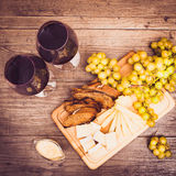 Cheese, toasted brown bread, two glasses of red wine. Horizontal. Cheese, toasted brown bread, two glasses of red wine. Top view. Warm colored. Horizontal Royalty Free Stock Photography
