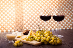 Cheese, toasted brown bread, two glasses of red wine. Horizontal. Cheese, toasted brown bread, two glasses of red wine on the wooden lattice background Stock Photography