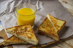 Cheese toasts for breakfast and orange juice in glass. Sandwich Royalty Free Stock Images