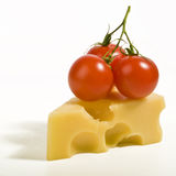 Cheese and tomato. A bunch of cherry tomato on a slice of cheese Royalty Free Stock Images