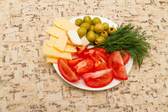 Cheese tomato green olives dill on a white plate on the  table. Cheese tomato green olives dill on a white plate on the kitchen table Stock Images
