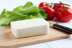 Cheese, tomato and lettuce. Cheese, tomato, lettuce and knife lie on a cutting board Royalty Free Stock Photography