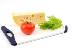 Cheese, tomato and salad sheet on a white board Stock Photos