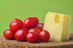 Cheese and tomato. Cheese and a tomato on trencher on  green background Stock Photos