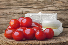 Cheese and tomato. Cheese and a tomato on trencher, wood background Royalty Free Stock Photo