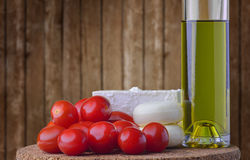 Cheese, tomato and virgin olive oil. Cheese, tomato and extra virgin (home made) olive oil on trencher, wood background Stock Photo