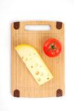 Cheese and tomato on a wooden board. Royalty Free Stock Image