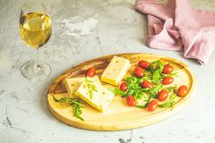 Cheese, tomatoes and arugula on the wooden plate. Delicious appetizer with white wine on the pink concrete table surface. Copy space  for you text royalty free stock photography