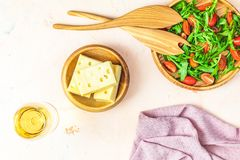 Cheese, tomatoes and arugula on the wooden plates. Delicious appetizer with white wine on the pink concrete table surface. op view, copy space  for you text stock images