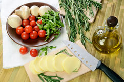 Cheese, tomatoes and herbs on a kitchen table top view Stock Images