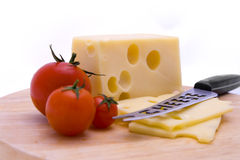 Cheese, Tomatoes and Knife Closeup. Closeup of swiss cheese, tomatoes and knife on a cutting board Stock Photo